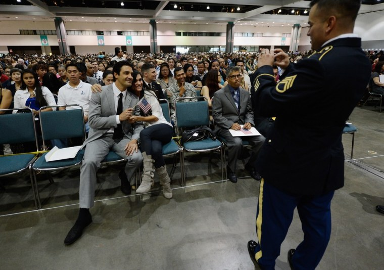 Gilles Marini, left, poses with the wife of his friend Regina Deleo as they get a picture taken by US Army Ssg. Fabrizio Bustos before Marini and Bustos took the oath of citizenship.