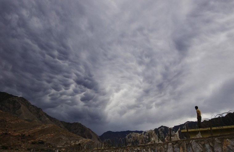 An Afghan National Army soldier stands on a roof to look at storm clouds passing over Combat Outpost Nangalam in the Pech River Valley of Afghanistan's Kunar Province on Thursday.