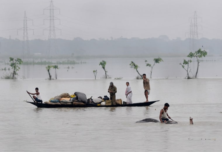 A mahout moves an elephant to higher ground as villagers paddle with their belongings through flood waters in the Pobitora Wildlife Sanctuary, some 55 km from Guwahati, the capital city of Assam, India on June 28, 2012.