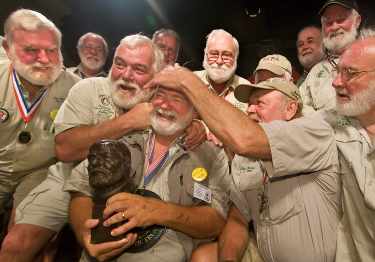 Charles Bicht is congratulated by previous winners of the annual Ernest Hemingway look-alike contest in Key West, Fla., on July 24, 2010.