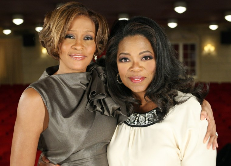 """In this Aug. 31, 2009, photo provided by Harpo Productions, television talk-show host Oprah Winfrey poses with Whitney Houston at the Town Hall in New York. Houston, who's new album \""""I Look To You\"""" was released on Aug. 31, is interviewed by Winfrey for a two-part season premiere of The Oprah Winfrey Show, airing Sept. 14 and 15. (AP Photo/Harpo Productions, George Burns)"""