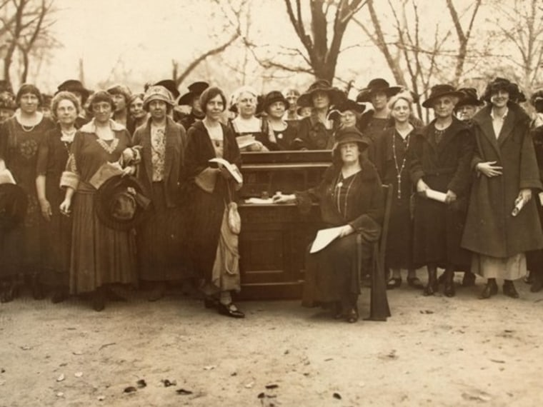 Suffragists Alice Paul, Alva Belmont (seated) and members of the National Woman's Party gathered around Susan B. Anthony's desk, circa 1922.