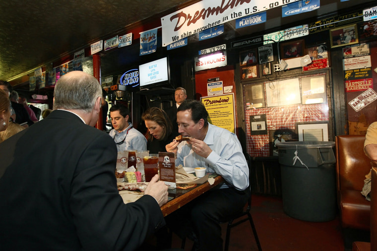 TUSCALOOSA, AL - MARCH 12: Republican presidential candidate, former U.S. Sen. Rick Santorum (R) eats ribs at Dreamland Bar-B-Que with his wife Karen Santorum during a campaign stop March 12, 2012 in Tuscaloosa, Alabama. As the race for delegates continues, Alabama and Mississippi will hold their primaries tomorrow. (Photo by Win McNamee/Getty Images)