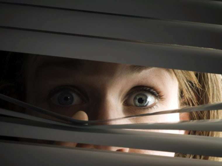Woman peeping through horizontal blinds scared hide hiding fear phobia afraid eyes peep spy spying msnbc stock photo photography