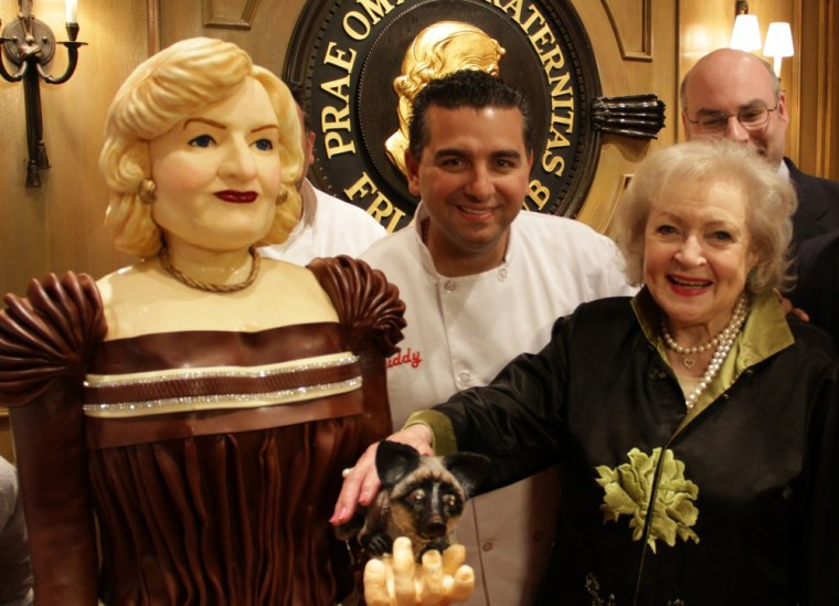 """Betty White poses with a life-size cake of herself created by """"Cake Boss"""" Buddy Valastro at her Friars Club roast on May 16."""