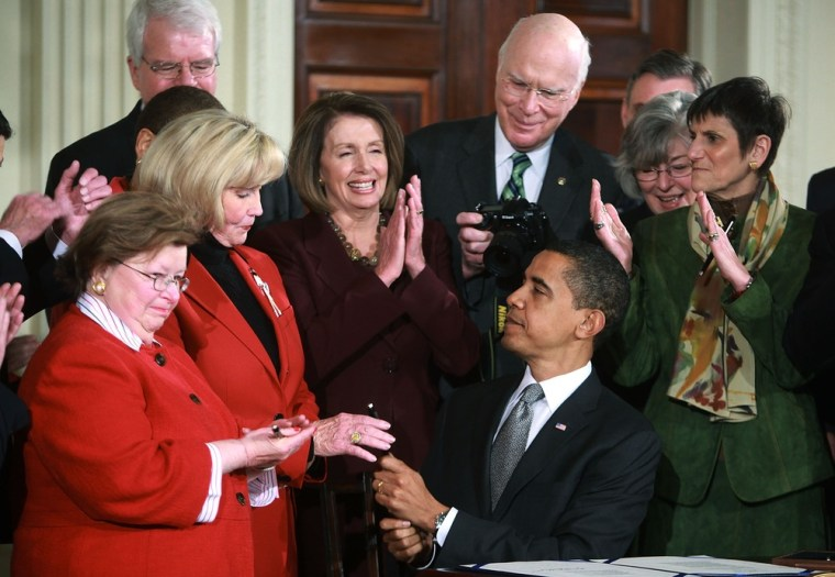 President Barack Obama, center, hands Lilly Ledbetter a pen after signing the Lilly Ledbetter Fair Pay Act on Jan. 29, 2009, in the White House.