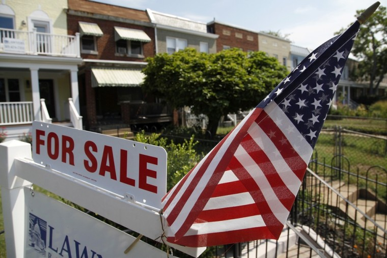 A U.S. flag decorates a for-sale sign at a home in the Capitol Hill neighborhood of Washington, DC. Home resales took a surprise rise in October.