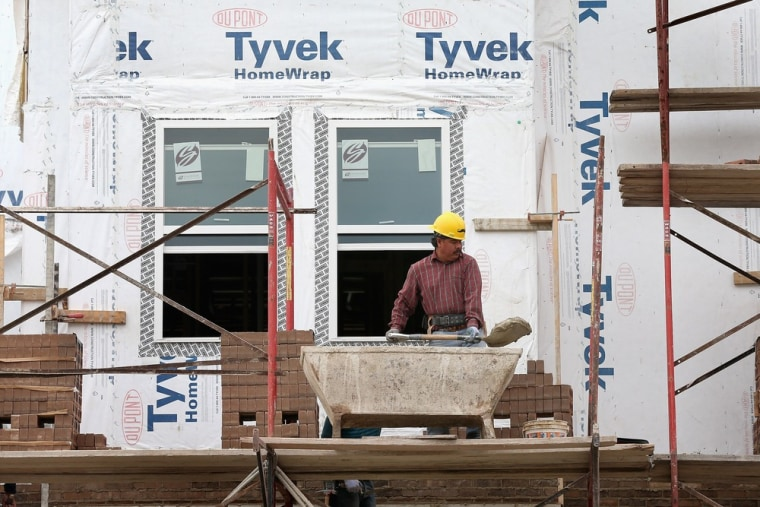 Workers put brick facing on a group of row houses under construction Oct. 17 in Chicago. The housing recovery is building up steam, but lenders need to loosen tight standards for it to accelerate further.