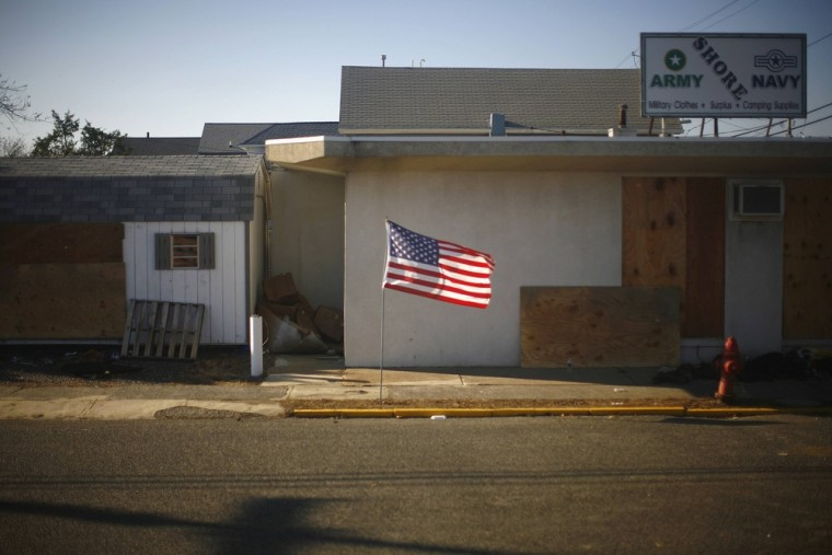 A flag is seen Nov. 11 in front of a business damaged by Hurricane Sandy in Seaside Heights, N.J. The shuttering of businesses across the region has put a dent in the labor market that could be felt for months.
