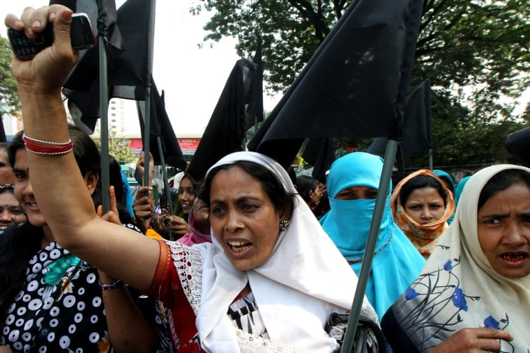 Bangladeshi garment workers shout slogans as they hold black flags during a protest in Dhaka on November 28, 2012 following a deadly fire in a garment...
