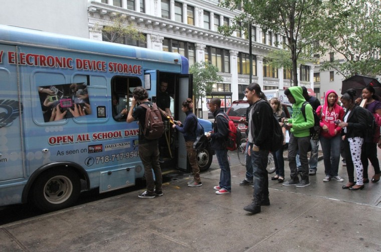 Students from New York's Washington Irving educational complex line up to leave their cellphones and other electronic devices, for a dollar a day per item, in a privately operated truck parked near their school.