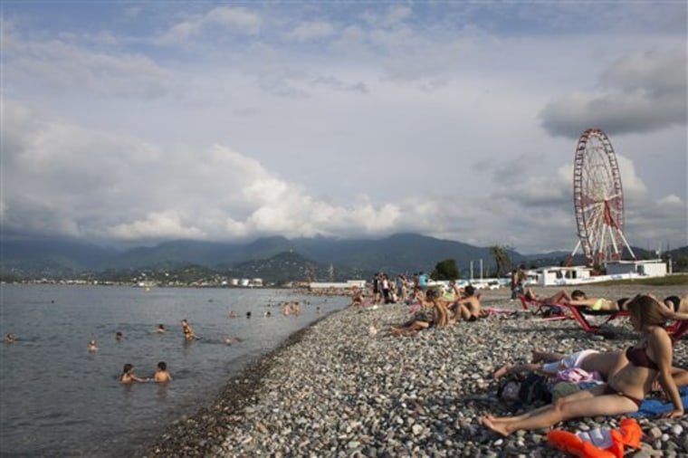 Tourists swim and sunbathe in the Black Sea resort town of Batumi in Georgia.
