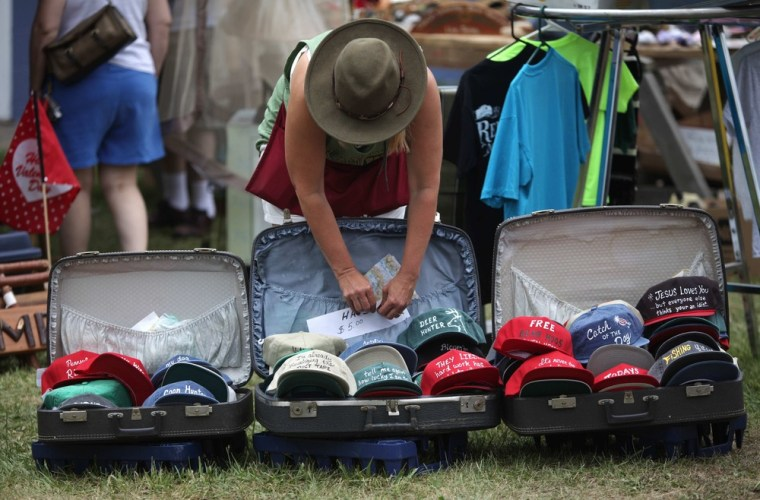 A seller works on her hat display at a yard sale, Such sales are one of many ways you can put extra money in your wallet.