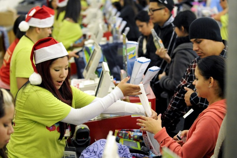 Shoppers pay for their purchases at an Old Navy store last holiday season. This year, overall spending is expected to be cautious, except when it comes to spending on ouselves.