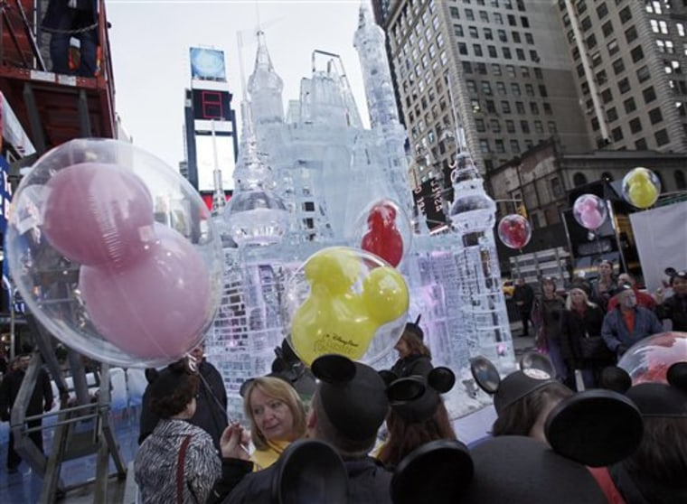 People with mouse ear caps and balloons gather near a three-story castle mad of ice in New York's Times Square. On Wednesday, Disney announced a new p...