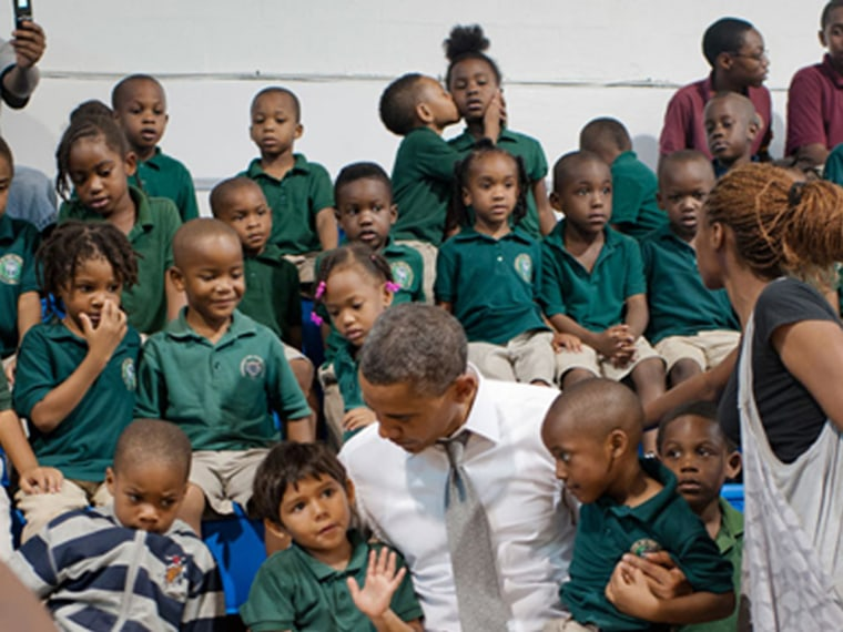 While President Barack Obama chats in the front row, the real action is happening behind him at a school on the campaign trail.