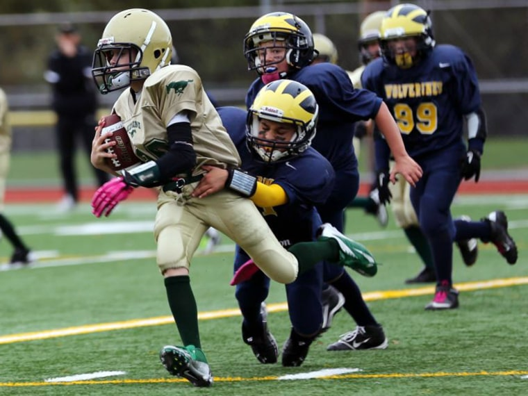 Hard knocks: 10-year-old Jayan White tackles an opponent.