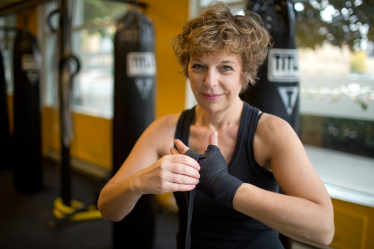 """You take a hit to your femininity,"" says Diane Mapes, seen here wrapping her hands before working out at Axtion Club boxing gym in Seattle. ""But your hair comes back, strength comes back, and my boobs will come back eventually."" Mapes had a double mastectomy in 2011."