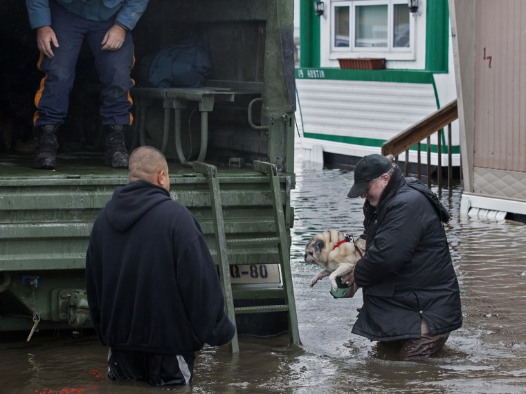 With the aid of New Jersey state police, a man walks with his dog to a National Guard vehicle after leaving his flooded home at the Metropolitan Trail...
