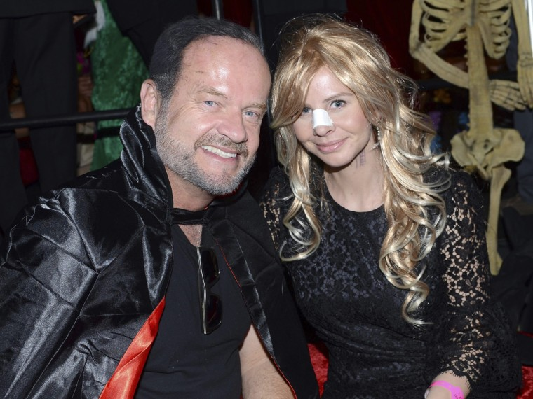 Actor Kelsey Grammer & wife Kayte pose at Playboy Magazine founder Hugh Hefner's annual Halloween Party, The couple took some heat for bringing their infant daughter along.