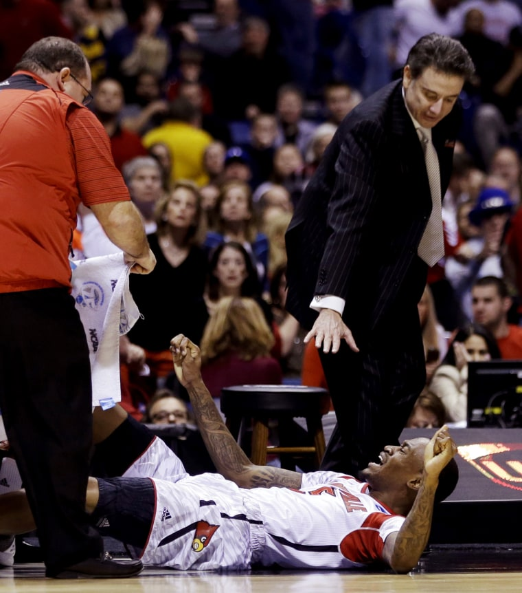 Louisville head coach Rick Pitino and trainers tend to injured guard Kevin Ware during the first half of the Midwest Regional final in the NCAA college basketball tournament against Duke, on March 31, 2013, in Indianapolis. Ware badly injured his lower right leg and had to be taken off the court on a stretcher.