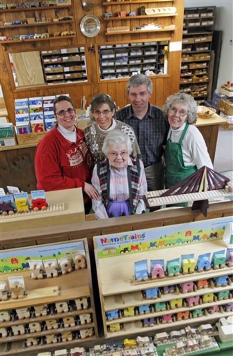 Image: Mike Rainville poses with his family members at the Maple Landmark Woodcraft factory in Middlebury, Vt.