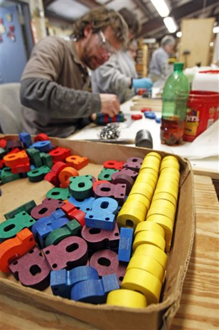 In this Friday, Feb. 22, 2013, photo, a worker assembles wooden toys at the Maple Landmark Woodcraft factory in Middlebury, Vt. Experts say family bu...