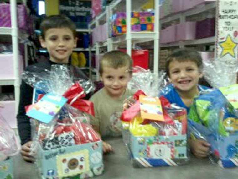 The Cervantes children in The Giving Village at Bright Blessings with gift sets they put together.