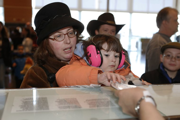 "Rebekah Tirrell and her mother Laura, both of Johnston, R.I., receive their boarding pass during  ""Wings For Autism"" program at Boston Logan Airport."
