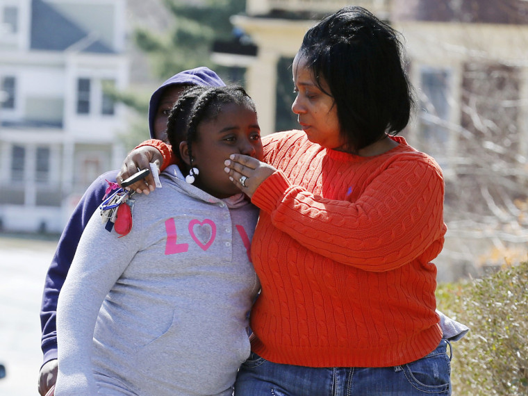 Tammy Lynch, right, comforts her daughter Kaytlyn, 8, after leaving flowers and some balloons at the Richard house in the Dorchester neighborhood of  ...