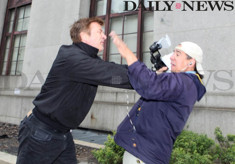 Alec Baldwin, left, scuffles with New York Daily News photographer Marcus Santos outside the Marriage License Bureau in New York on Tuesday morning.