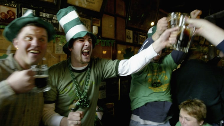 Revelers clink beer glasses and enjoy themselves during an all day party at historic McSorley's Old Ale House March 17, 2004, in New York.