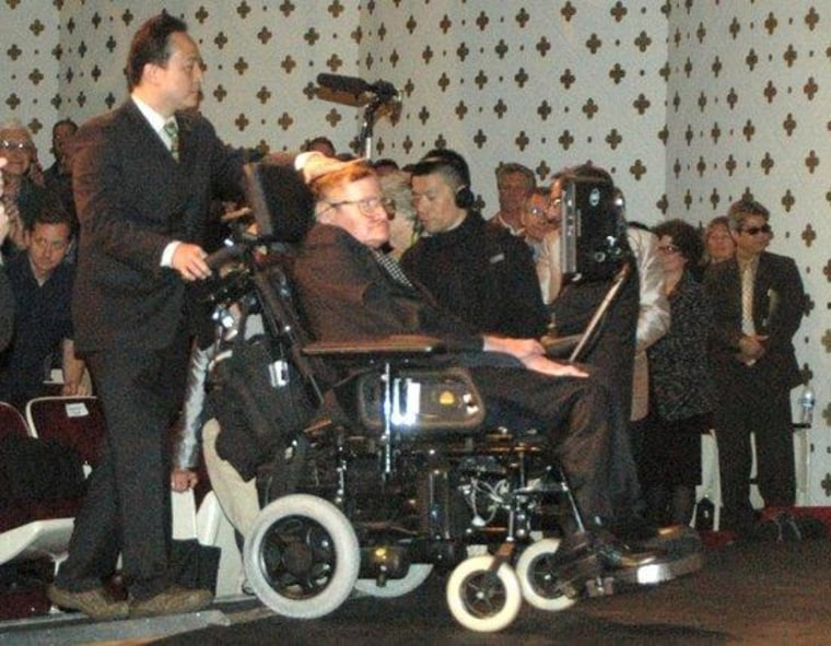 Stephen Hawking is brought onstage by a helper to give his presentation,
