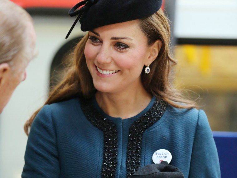 """Britain's Catherine, Duchess of Cambridge holds a """"Baby on board!"""" badge given to her during her visit to Baker Street underground station in London M..."""