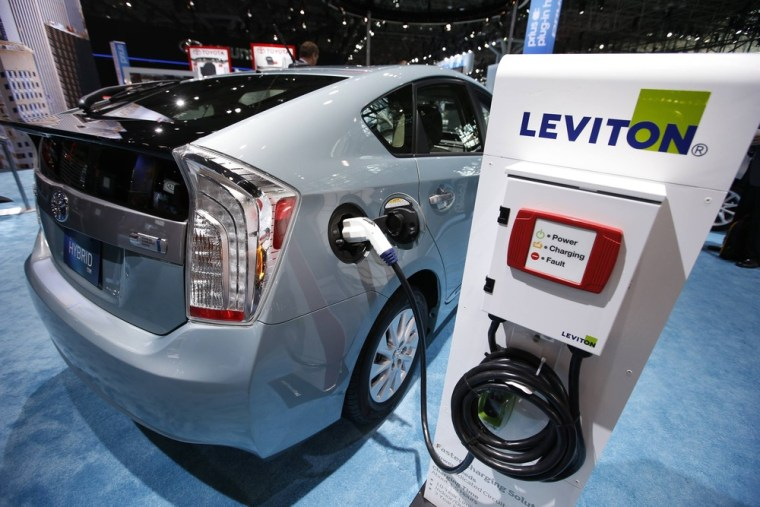 A 2013 Toyota Prius plug-in Hybrid car is plugged into a Leviton charging station at the Toyota display during a media preview at the 2013 New York In...
