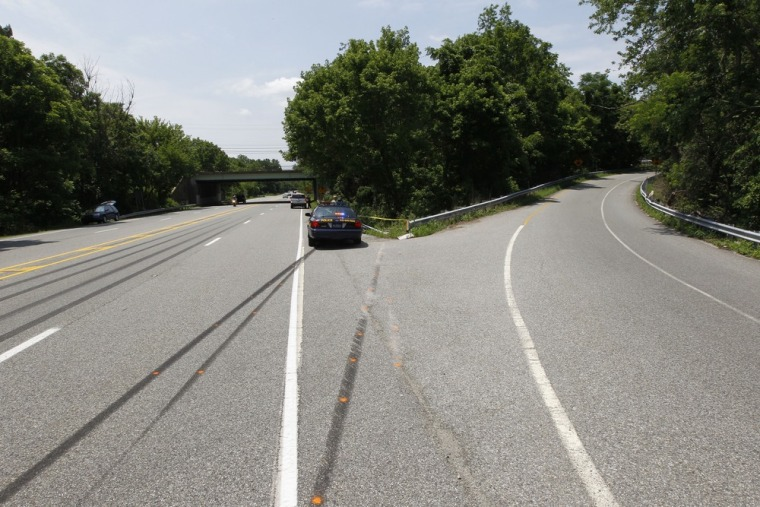 A police car sits near skid marks leading to where Ryan Dunn's Porsche left the road on Monday, June 20, in West Chester, Pa.