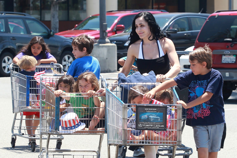 Nadya Suleman uses four shopping carts to haul her family to an L.A. grocery store.