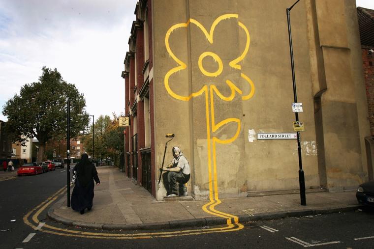 A woman walks past a piece by self-styled guerilla artist Banksy in London in November.