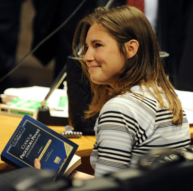 U.S. murder suspect Amanda Knox holds the Italian penal code book at the trial of slain British student Meredith Kercher in Perugia January 16, 2009. ...