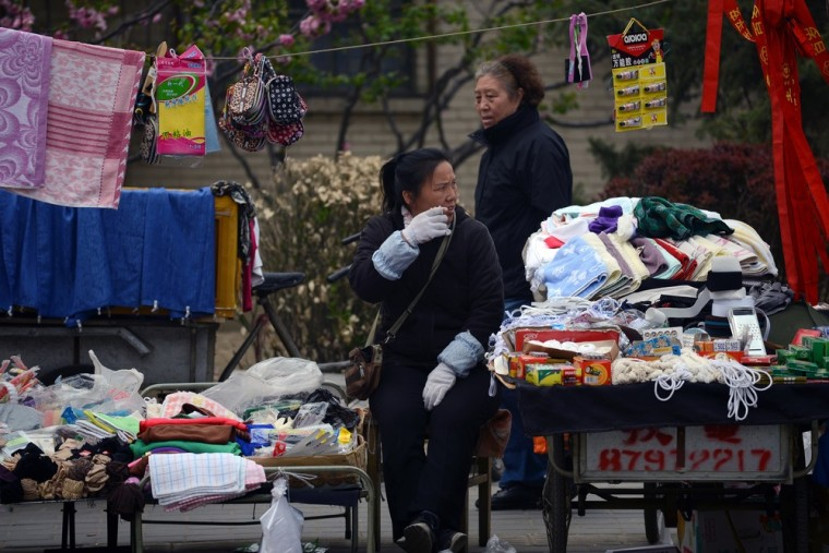 A vendor (front) sits by a road as she waits for customers in Beijing on April 23, 2013. Slower growth in China and Europe may be good news for Ameri...