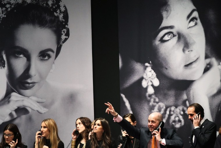 Auction house employees speak on the phone to bidders under pictures of Elizabeth Taylor at Christie's, where hundreds of items once belonging to the iconic actress went on the auction block in New York.