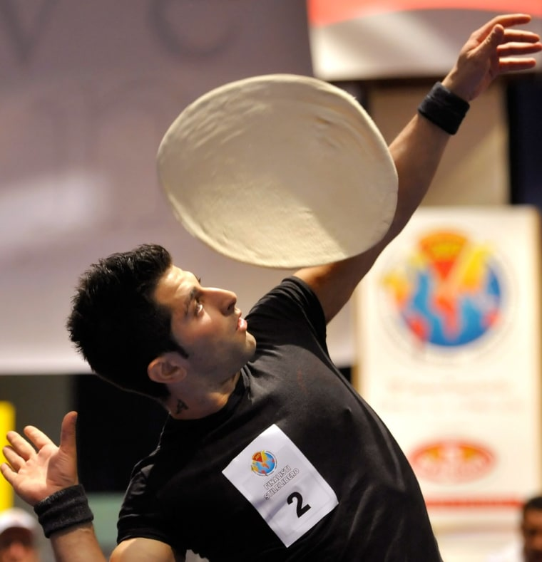 Alessandro Colluccino, of Italy, performs with his dough during an acrobatic pizza event in this file photo from. Italy is facing a crisis: a shortage...