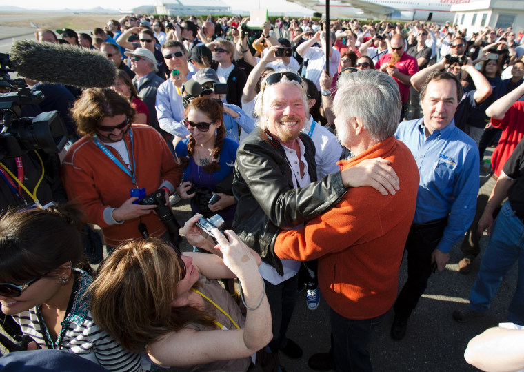 A bearded Richard Branson (center) gets a congratulatory hug from SpaceShipTwo designer Burt Rutan. Sierra Nevada Corp.'s Mark Sirangelo, who was involved in the development of SpaceShipTwo's hybrid rocket engine, can be seen just to the right of Rutan.