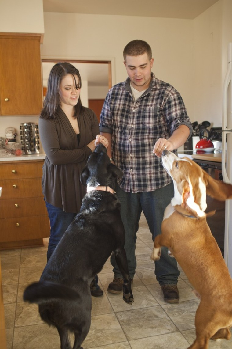 Brian and Katie Delano play with their dogs at their home in Tacoma, Wash.