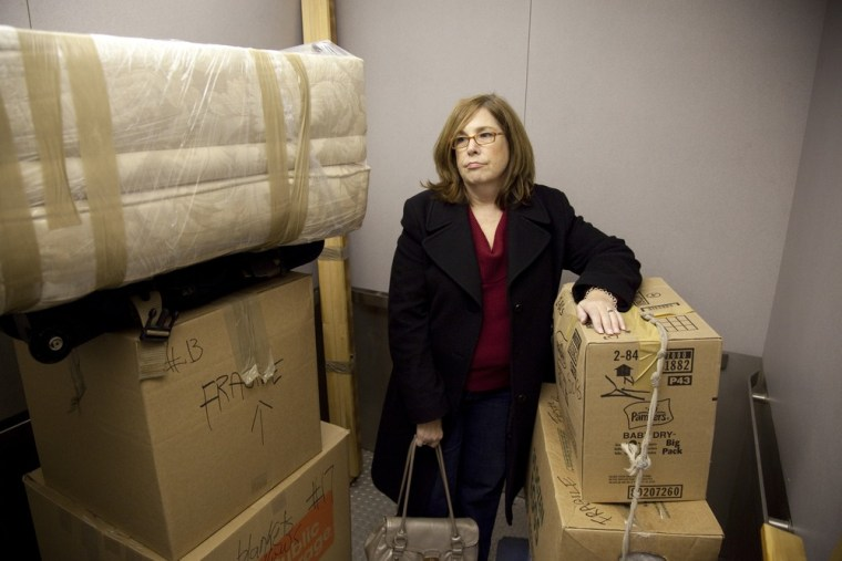 Ann Valencia looks on as movers unload a truck full of her belongings and load them into a storage unit she rented. Valencia has had to downsize and move in with a friend after she could no longer afford her two-bedroom apartment in Bayside, New York.