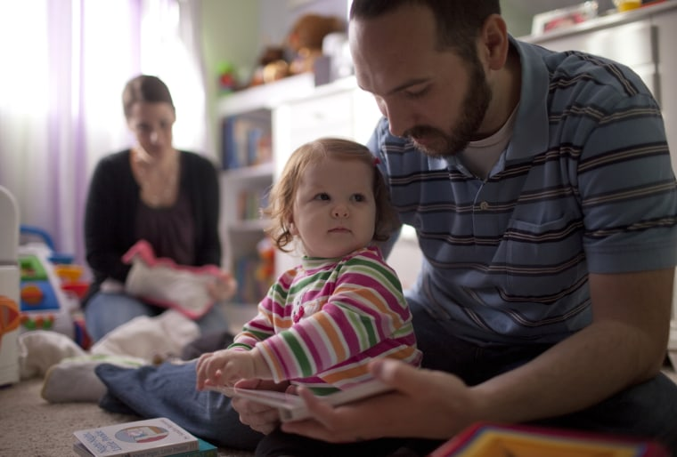 Jeremy Wilson reads to his 14-month-old daughter Samantha while his wife Jamie folds diapers in their Anderson, Calif. home. The Wilsons feel squeezed on their $50,000-a-year income.