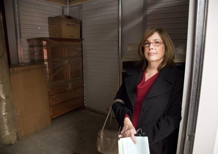 Ann Valencia looks on as movers unload a truck full of her belongings and load them into a storage unit she rented. Valencia has had to downsize and move in with a friend