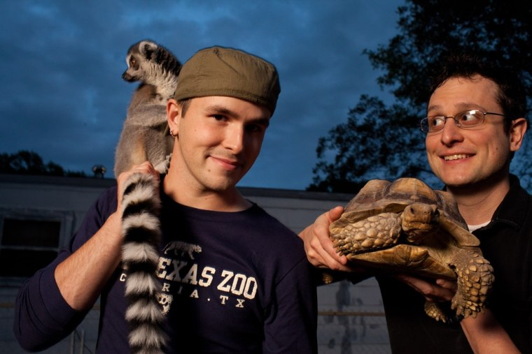 Nathan Palmer, left, and ring-tailed lemur, Grover, with partner Brett Jones, holding African spur thigh tortoise, Shelly, at their home in Victoria, Texas.