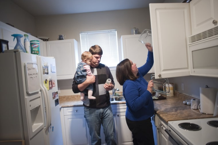 Samuel and Megan Moss stand in their kitchen with their 10-month-old daughter, Mary Margaret, at their apartment in Plano, Texas.