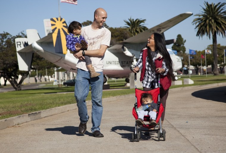 Jason Ruediger carries his 2-year-old daughter, Aureus, while his wife pushes their 1-year-old son, Crichton, on the Naval Air Station North Island in Coronado, Calif.